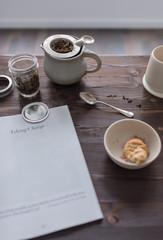 dunkler Tisch aus Holz mit Tee, Zeitung und Keksen