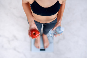 Sporty woman with a perfect body measuring body weight on electronic scales and holding a bottle of water and a red apple. Healthy low calorie meals, fruits. Diet, a healthy lifestyle. Weight loss.