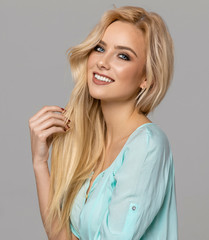 Portrait of blond smiling female model with blue eyes