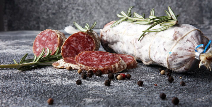 sliced salami and salami sausage on grey background