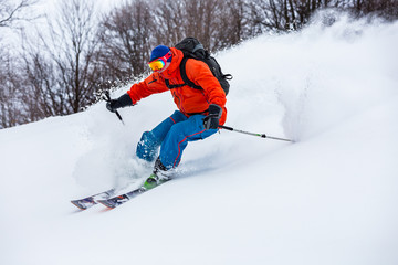 Fototapete - Powder day in Carpathian mountains. A skier is riding down the hill.
