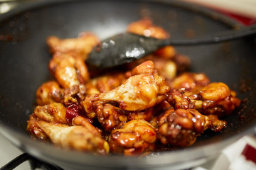 Chicken wings caramelizing in the pan
