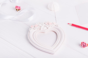 Heart shaped photo frame with clipping path of the gypsum, red pencil, greeting card on the white wooden table. Gifts for Valentine's Day for a loved one. Selective focus.