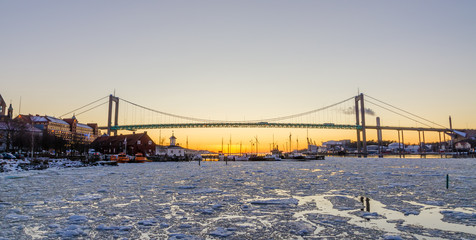 Gothenburg - Beautiful sunset at frozen Gota river with Hisingsleden Bridge in the harbor district during winter