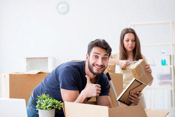 Young family unpacking at new house with boxes