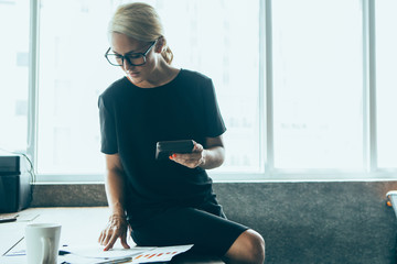 Confident female accountant counting on calculator