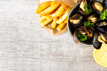 Mussels with herbs in a bowl with lemon and French fries on a white wooden board. Seafood. Food at the shore of the French Sea. Dark background. Top view