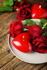 Wall Mural - Red candles and roses on the wooden table