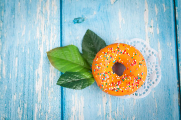 Orange sweet donut with green flower leaves