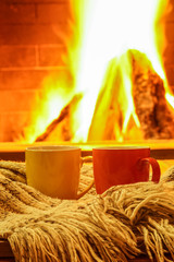 Two mugs for tea or coffee, wool things against cozy fireplace background, winter vacations, country house, selective focus, horizontal.