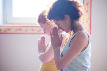 couple of women on yoga class closeup of hands in namaste gesture indoor