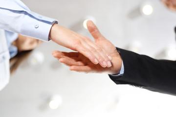 Gratulacje. Powitanie nowego pracownika firmy. Dłoń kobiety i mężczyzny w  strojach biurowych podczas gestu przywitania.