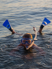 A teenager wearing a mask with tube   for diving and flippers background of the sea.
