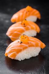 Three Sushi nigiri with salmon on black background