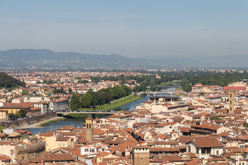 Florentine cityscape with red roofs, Arno river and hills on background in a sunny day, Tuscany, Italy.