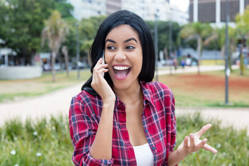 Native latin american young adult woman laughing at phone