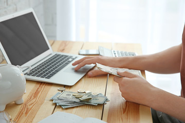 Young man using laptop while counting money at table, closeup