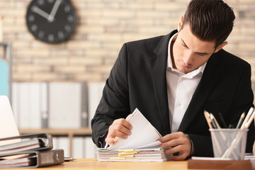 Young man working with documents in office