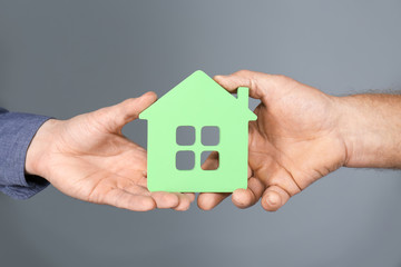 Real estate agent and senior man holding house model on grey background