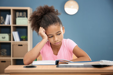 Tired African-American girl with textbook in classroom