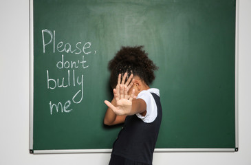 "African-American girl near chalkboard with text ""Please don't bully me"""