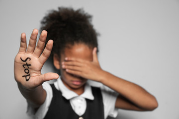 "Little African-American girl with word ""Stop"" on light background"