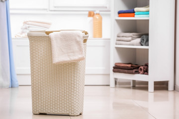 Plastic laundry basket with towel indoors