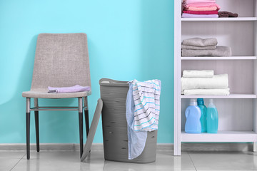 Plastic laundry basket with clothes indoors