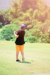 Golfer hitting golf shot with club on course while on summer vacation,boy playing golf on a golf course in the sun