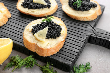Slices of bread with black caviar and butter on wooden board