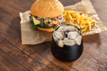 Glass of cold cola with tasty burger on table