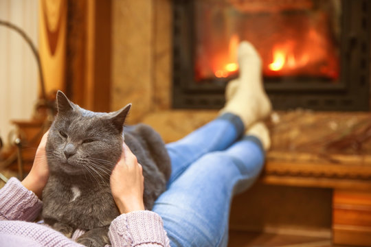 Woman with cute cat resting near fireplace at home