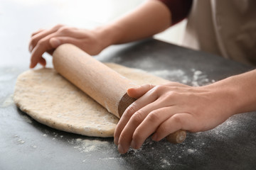 Woman rolling dough with poppy seeds on table, closeup