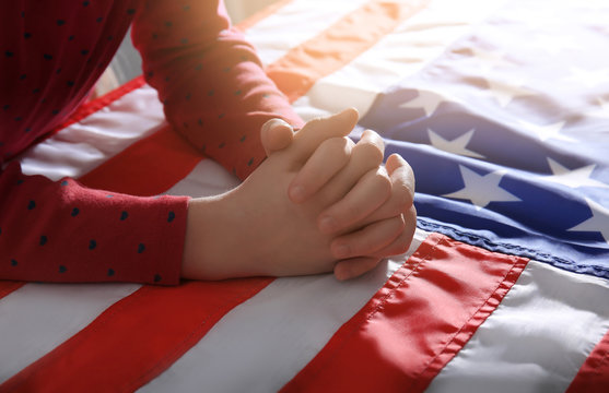 Little girl praying over American flag, closeup