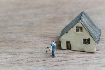 Lovely couple with success future house concept, small miniature marriage couple with ceramic house on wood table, can be used as investment, mortgage or love life motivation