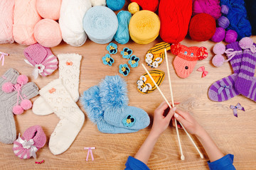 Dressmaker workplace. Female woman hands knitting colorful warm socks with knitted needles and red, blue, pink and pink balls of thread
