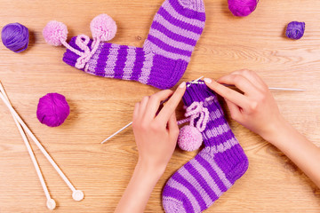 Woman female girl knits a new warm striped violet socks on wooden background. Dressmaker workplace. Top view
