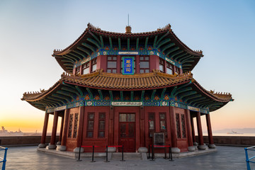 """Zhanqiao pier at sunrise, Qingdao, Shandong, China. The name """"Huilan Pavilion"""" is engraved above the entrance door."""