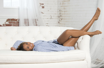 Beautiful and silly young woman wearing a men's blue striped shirt lounges on a white couch