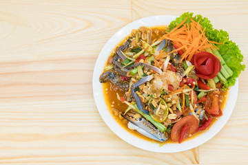 Papaya salad with BLUE SWIMMING CRAB on wood table.