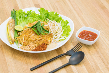 Top view food : Pad Thai, Stir-fried rice noodle with egg, tofu on wooden table. Famous Thai street food in Thailand.