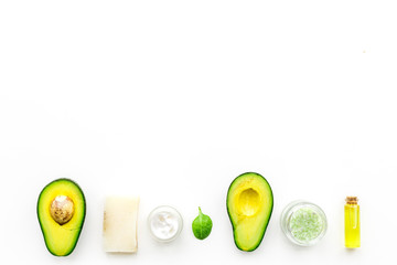 Cosmetics based on avocado oil. Cream, soap, spa salt on white background top view copy space