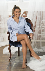 Beautiful and sexy young biracial woman wearing a men's blue striped shirt sits in a vintage blue upholstered chair
