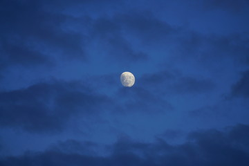 View of the moon in a dark blue sky partially covered by clouds