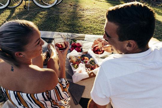 Romantic couple having a picnic at sunset