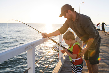 father teaching little young son to be a fisherman, fishing together on sea dock embankment enjoying and learning using the fish rod