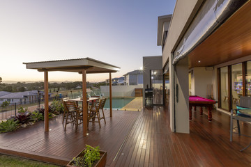 Backyard patio setting with swimming pool at sunset