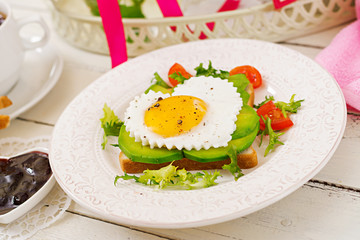 Breakfast on Valentine's Day - sandwich of fried egg in the shape of a heart, avocado and fresh vegetables. Cup of coffee. English breakfast.