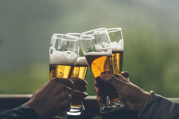 Canvas Prints Beer / Cider Beer with foam light tall boys in the hands of friends raising a toast closeup