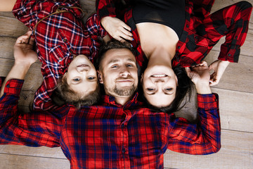 Happy beautiful happy family together at home lying on the wooden floor top view